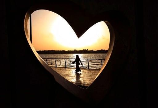 (AP Photo/Hasan Jamali, File). FILE -- In this May 11, 2014 file photo, a Saudi woman seen through a heart-shaped statue walks along an inlet of the Red Sea in Jiddah, Saudi Arabia.
