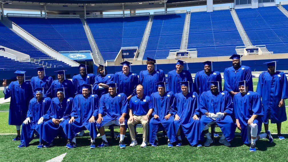 UK football coach Mark Stoops poses with players who enter the coming season with degrees already in hand. (WDRB photo by Eric Crawford)