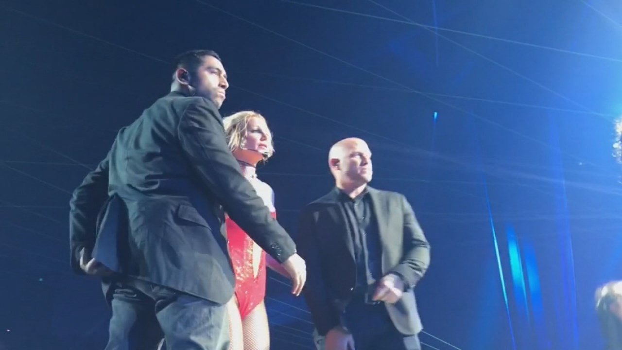 Britney Spears is escorted off stage after a fan jumped on stage and did a flip.