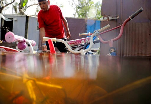 (AP Photo/David Goldman). Children's bicycles are flooded outside a home as Ezequiel Cruz retrieves belongings in the aftermath of Hurricane Irma in Bonita Springs, Fla., Tuesday, Sept. 12, 2017.