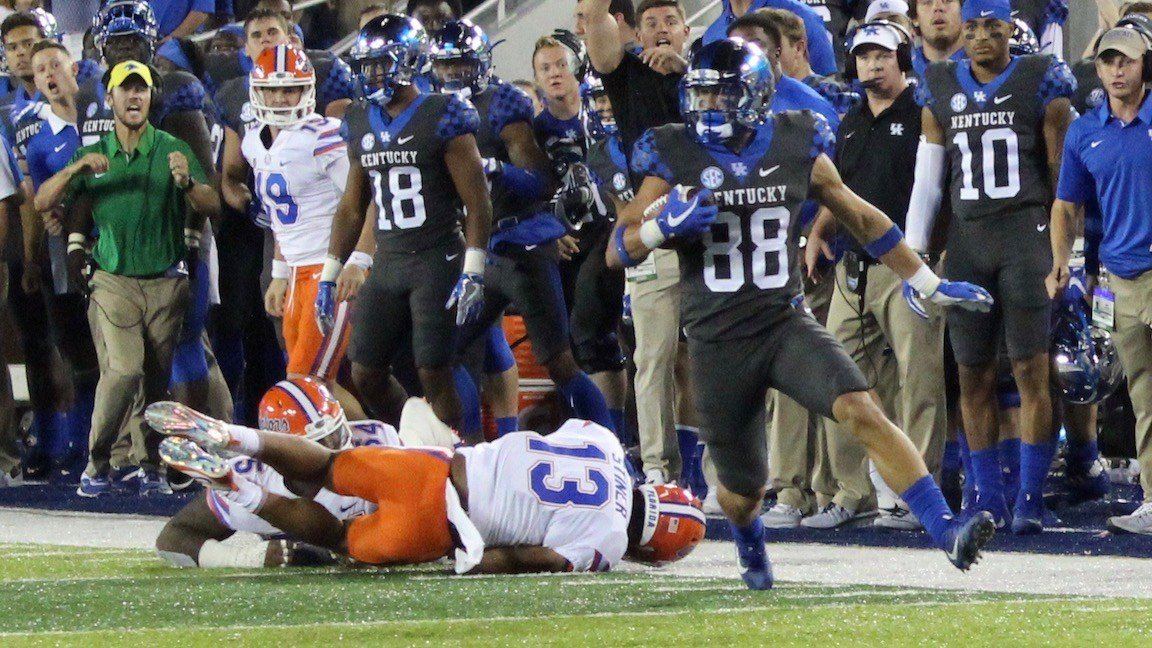Kentucky wideout Charles Walker shakes two Florida defenders during a punt return in Saturday's loss. (WDRB photo by Eric Crawford)