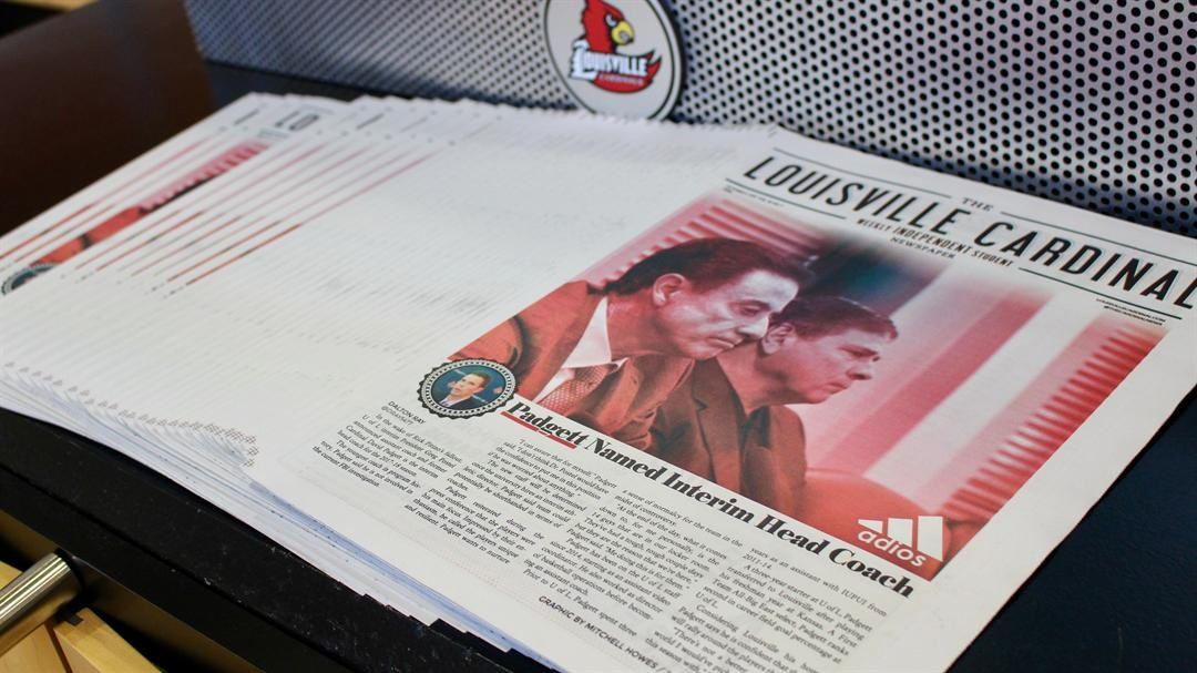 A stack of student newspapers proclaims David Padgett as the acting basketball coach in the lobby of the Louisville basketball practice facility (WDRB photo by Eric Crawford)