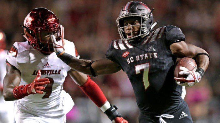 NC State back Nyheim Hines pushes Louisville tackler C.J Avery out of the way during the Wolfpack's 39-25 win. (AP Photo.)