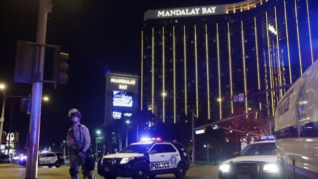 (AP Photo/John Locher, File). FILE - In this Sunday, Oct. 1, 2017 file photo, police officers stand along the Las Vegas Strip near the Mandalay Bay resort and casino during a shooting at a country music festival, in Las Vegas.