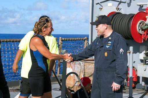 (Mass Communication Specialist 3rd Class Jonathan Clay/U.S. Navy via AP). In this Wednesday, Oct. 25, 2017 photo, USS Ashland Command Master Chief Gary Wise welcomes aboard Jennifer Appel, one of two Honolulu women and their dogs lost at sea for months.