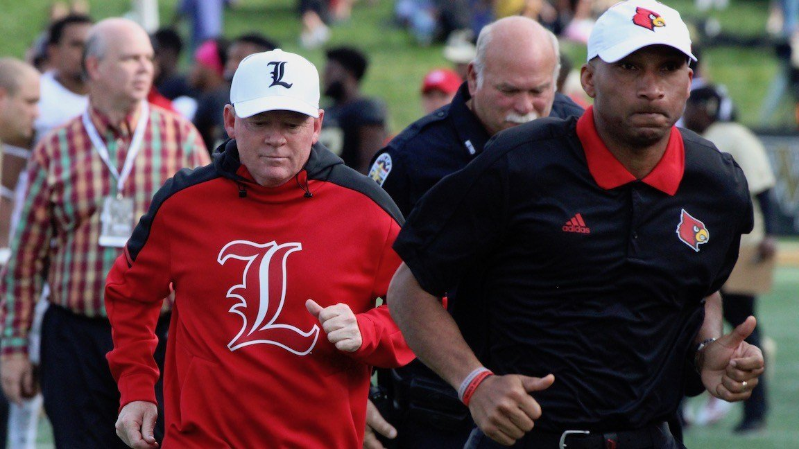 Louisville coach Bobby Petrino and assistant Lonnie Galloway leave the field after Wake Forest's 42-32 win on Saturday. (WDRB photo by Eric Crawford)