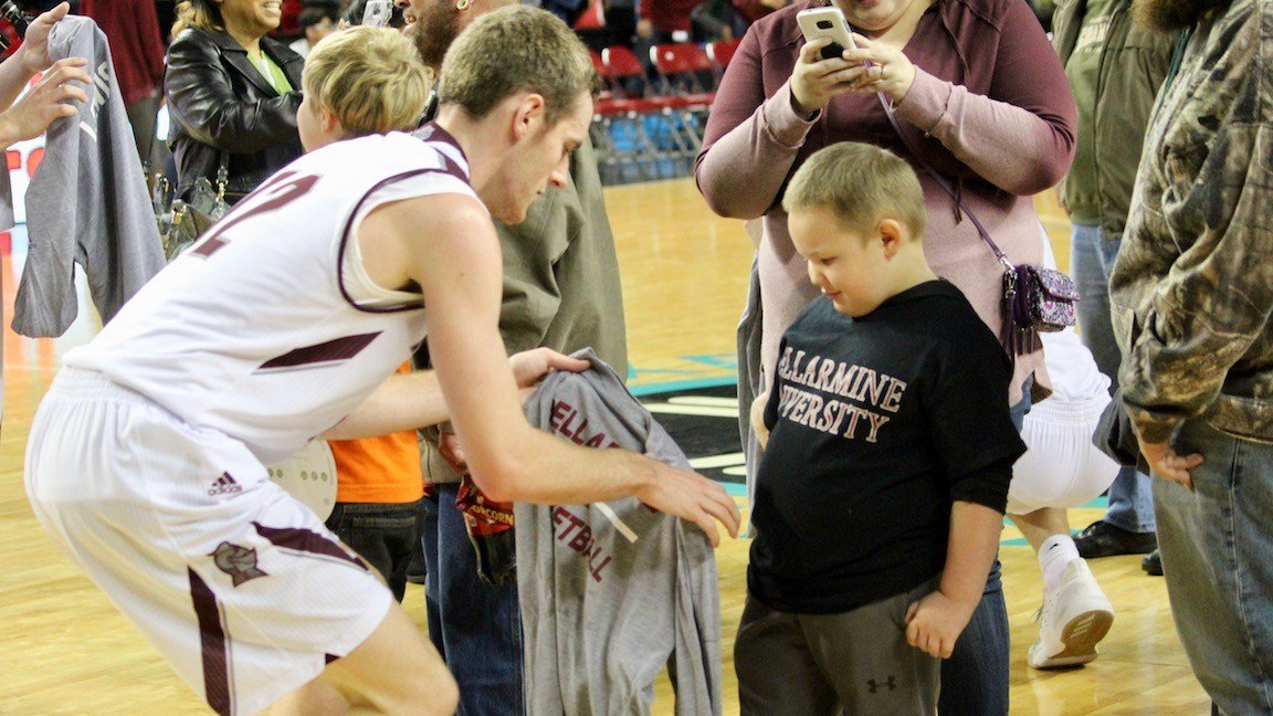 Bellarmine's Daniel Ramser presents a warm-up jersey to a young fan from Norton Children's Hospital's oncology unit. (WDRB photo by Eric Crawford)