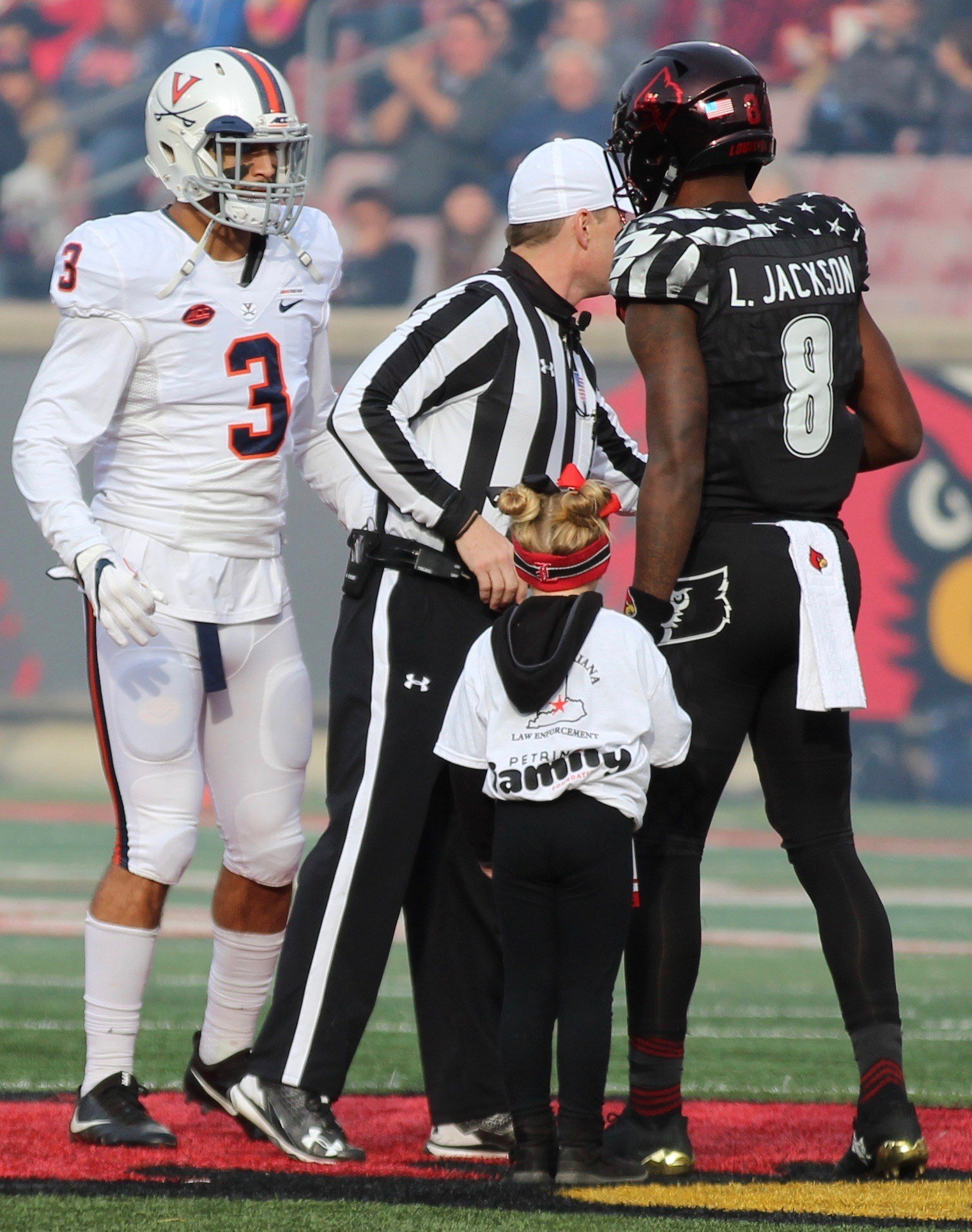 Lamar Jackson holds the hand of a young fan during the coin toss (WDRB photo by Eric Crawford)