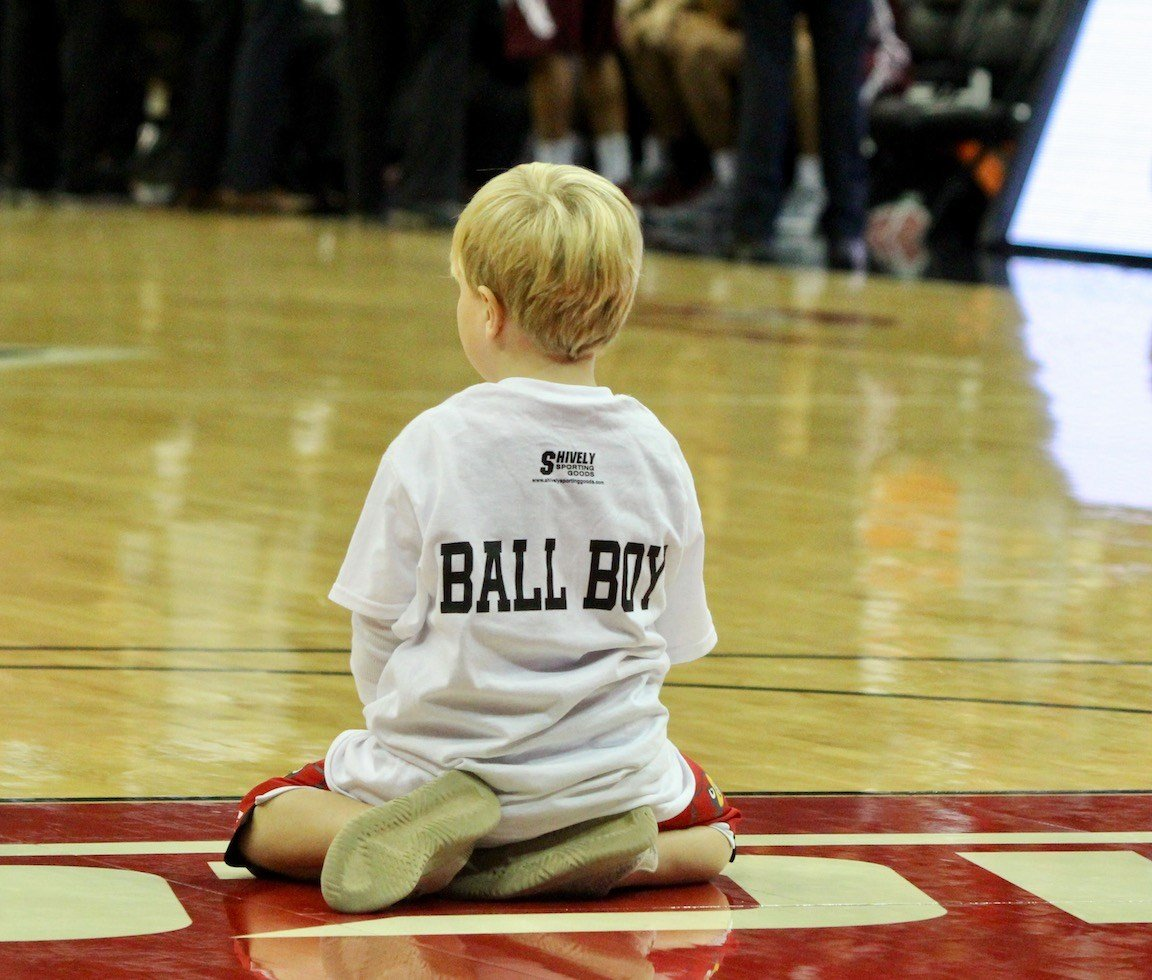 A young ball boy takes a break and takes it all in during a timeout in Louisville's win over SIU. (WDRB photo by Eric Crawford)