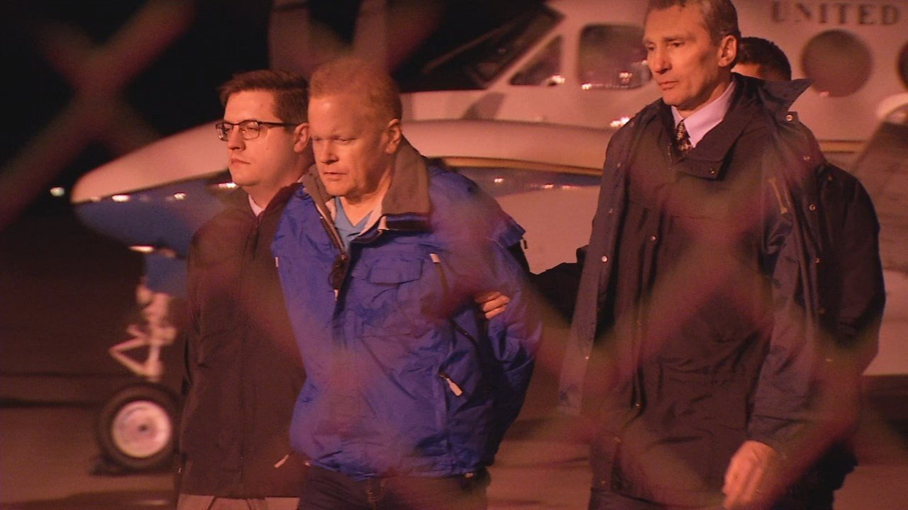 Eric Conn is escorted from his plane after being extradited from Honduras.