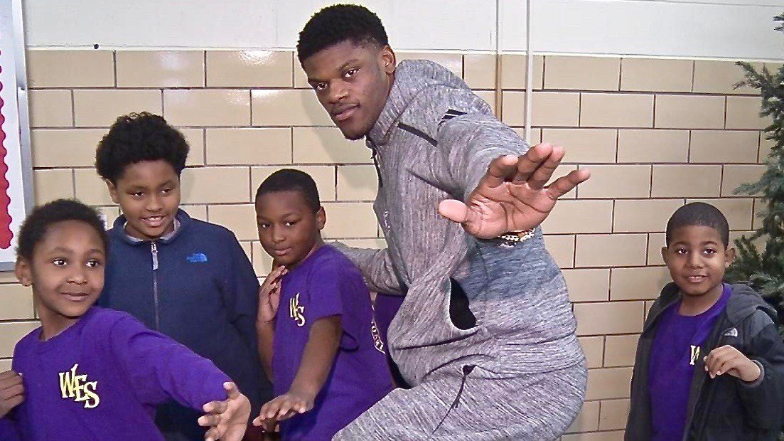 Lamar Jackson poses with students at Louisville's West End School on Thursday before leaving for Heisman festivities in New York. (WDRB photo by Katie George)