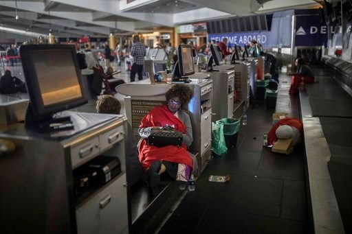 (AP Photo/Branden Camp). Passengers rest behind the ticket counter after the lights went out at Hartfield-Jackson Atlanta International Airport, Sunday, Dec. 17, 2017, in Atlanta.