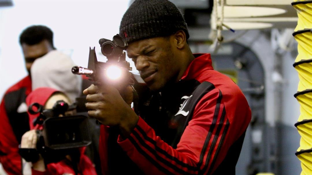 Lamar Jackson gets the feel for an M-4 rifle during a Naval tour in Jacksonville this week. (WDRB photo by Eric Crawford)