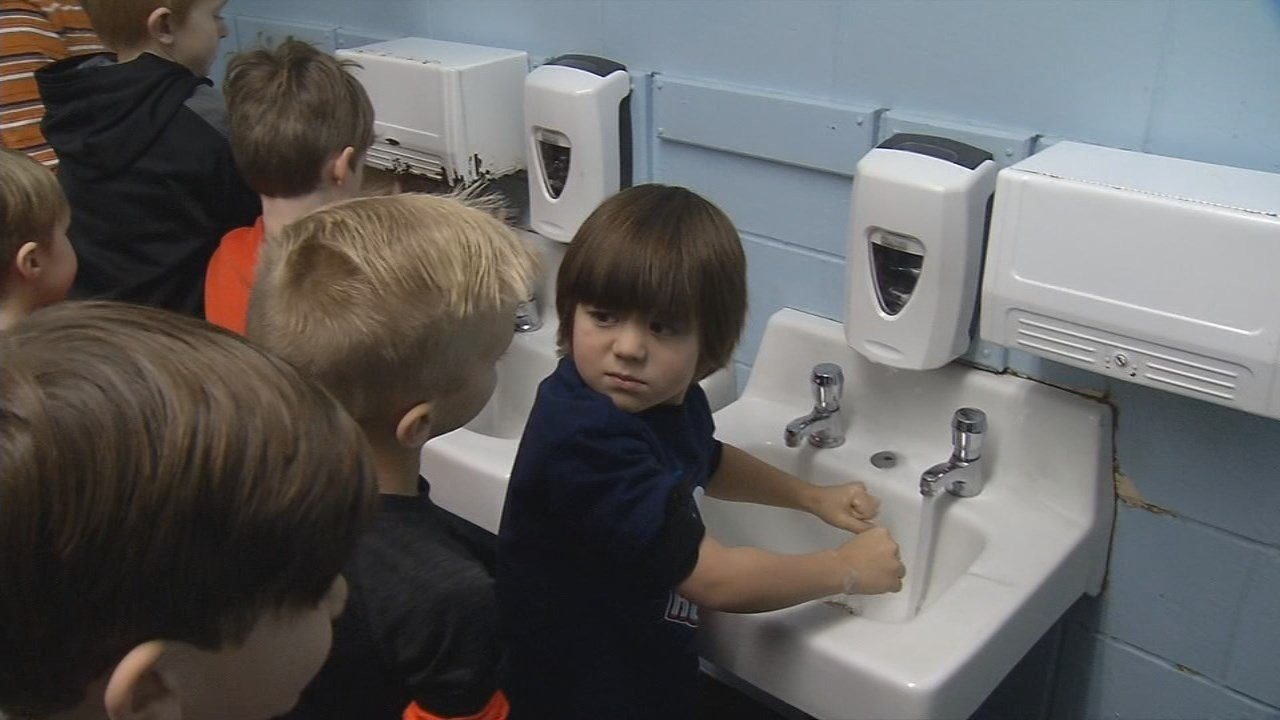 A student at Field Elementary in Louisville pauses before washing his hands.