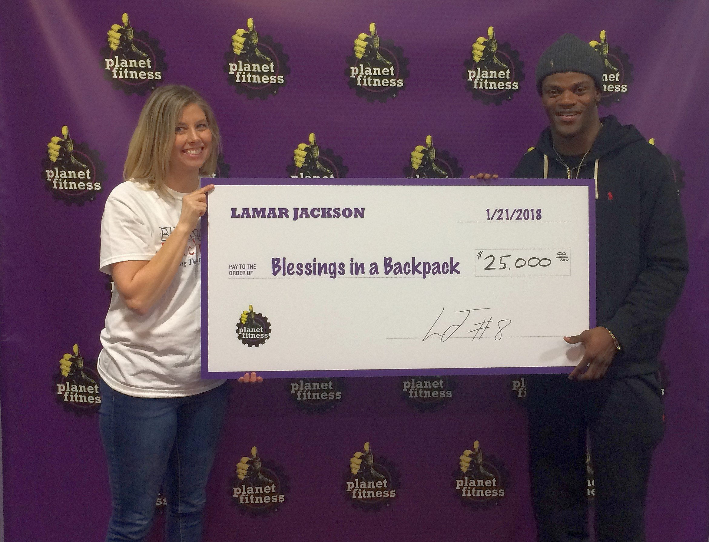 Blessings in a Backpack Chief Marketing Officer Nikki Grizzle receives a $25,000 donation check from Lamar Jackson. The $25,000 was raised through autograph sessions at four Louisville-area Planet Fitness clubs.
