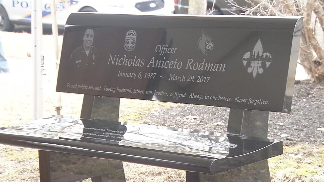 The bench has Rodman's picture on it, and a message saying he died protecting the citizens of Louisville.