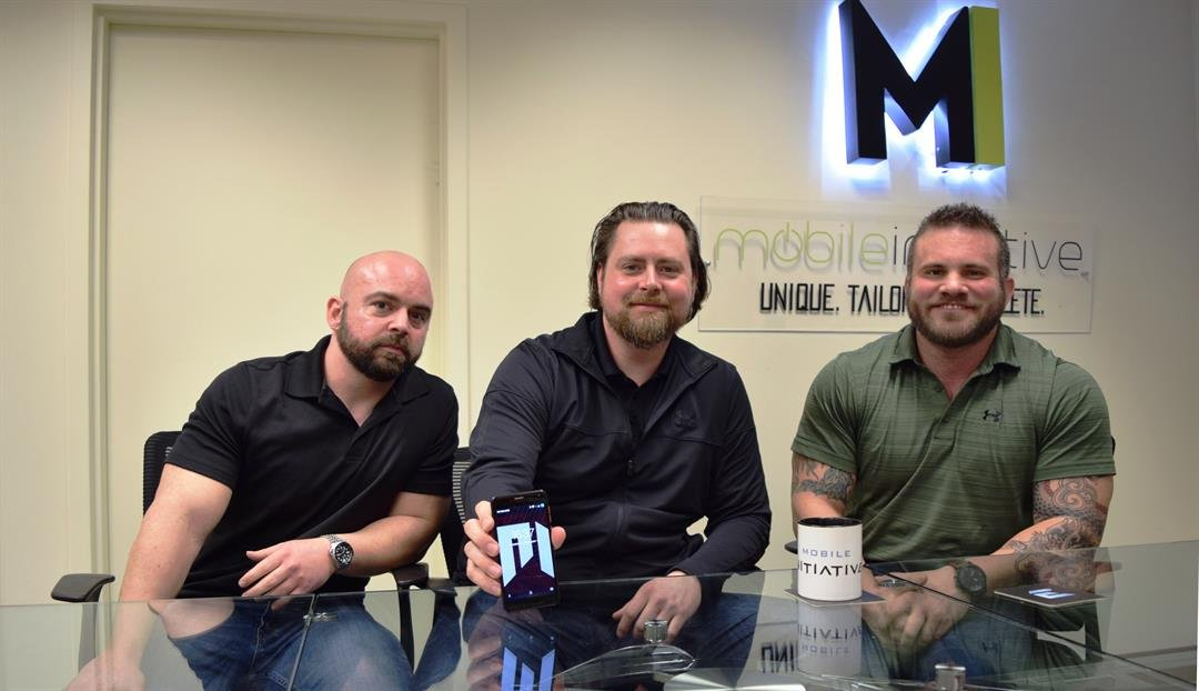 Mobile Initiative founders Brandon Wimsatt, Stephen Thompson and Mike Dahl at the company's office in Hurstbourne on Wednesday. Thompson holds a prototype of the Ethos, a bare-bones smartphone that the company will sell for $169.