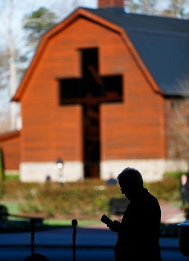 (AP Photo/John Bazemore). An usher reads a program ahead of a funeral service at the Billy Graham Library for the Rev. Billy Graham, who died last week at age 99, Friday, March 2, 2018, in Charlotte, N.C.