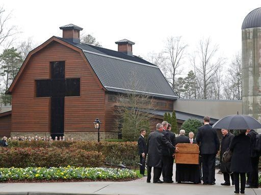 (AP Photo/Chuck Burton). Pallbearers carry the casket of the Rev. Billy Graham past family members as it returns to the Billy Graham Library in Charlotte, N.C., Thursday, March 1, 2018. His funeral will be Friday.