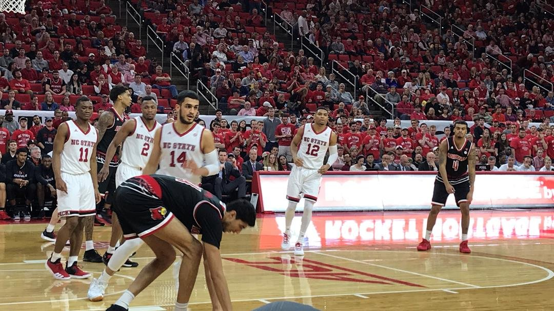 A string of turnovers, like this misplay between Quentin Snider (4) and Anas Mahmoud stopped Louisville against NC State Saturday night.