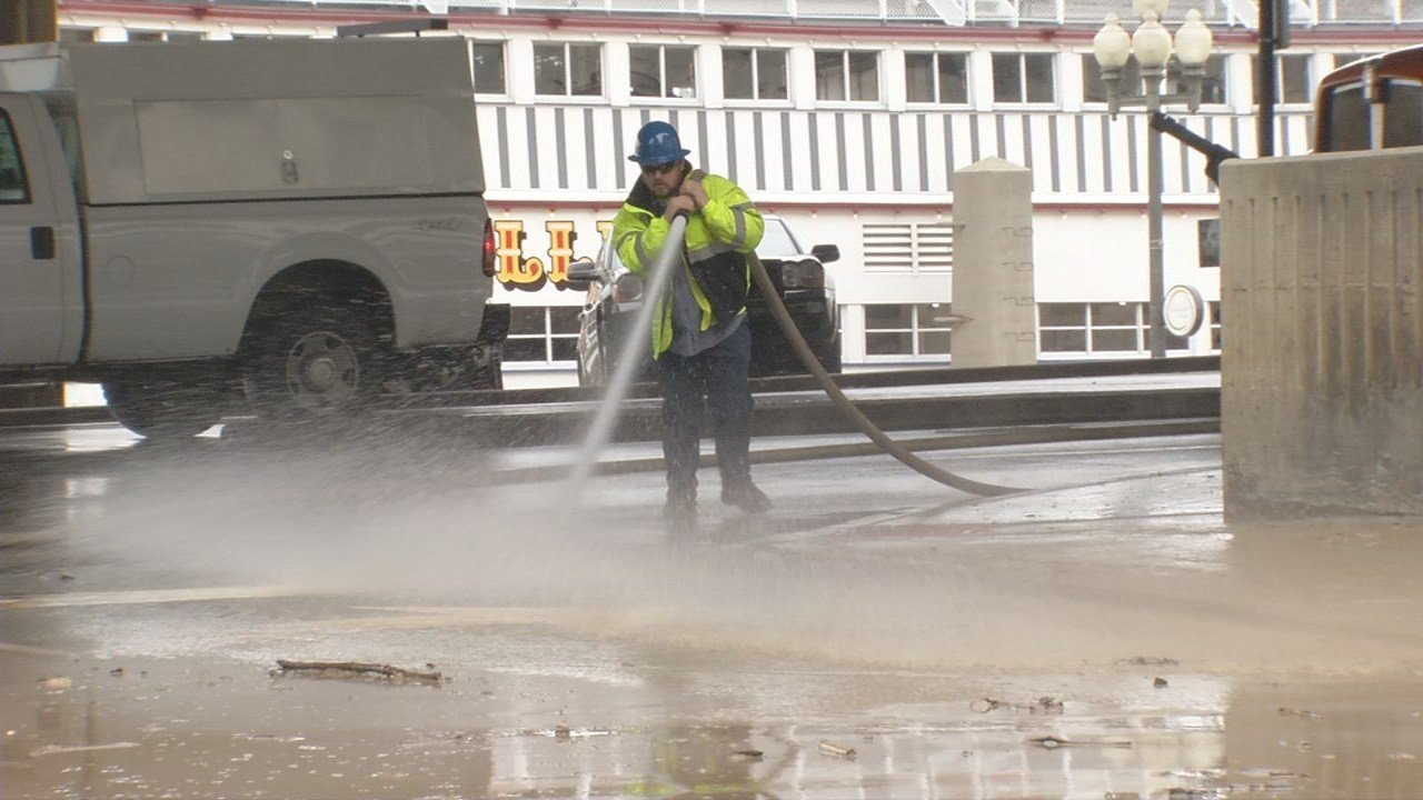 Crews spray the pavement to clean mud left behind by flood waters in downtown Louisville after the wettest February in decades.