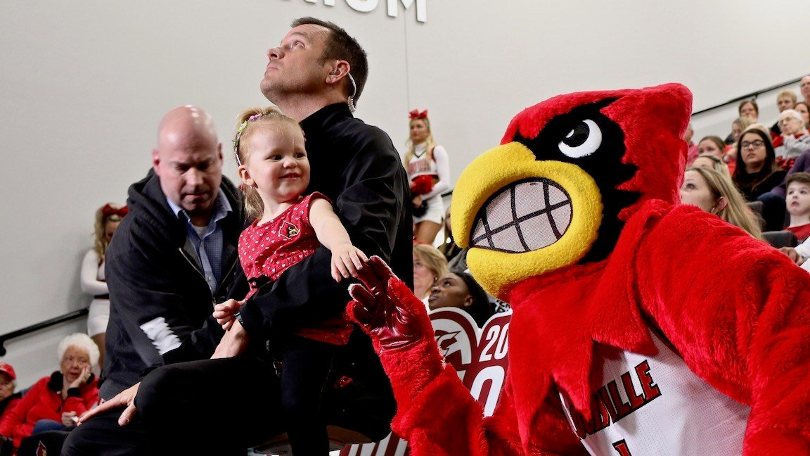 Jeff Walz's daughter, Lucy, plays with the Louisville mascot while her dad gets ready to go on ESPN. (WDRB photo by Eric Crawford)