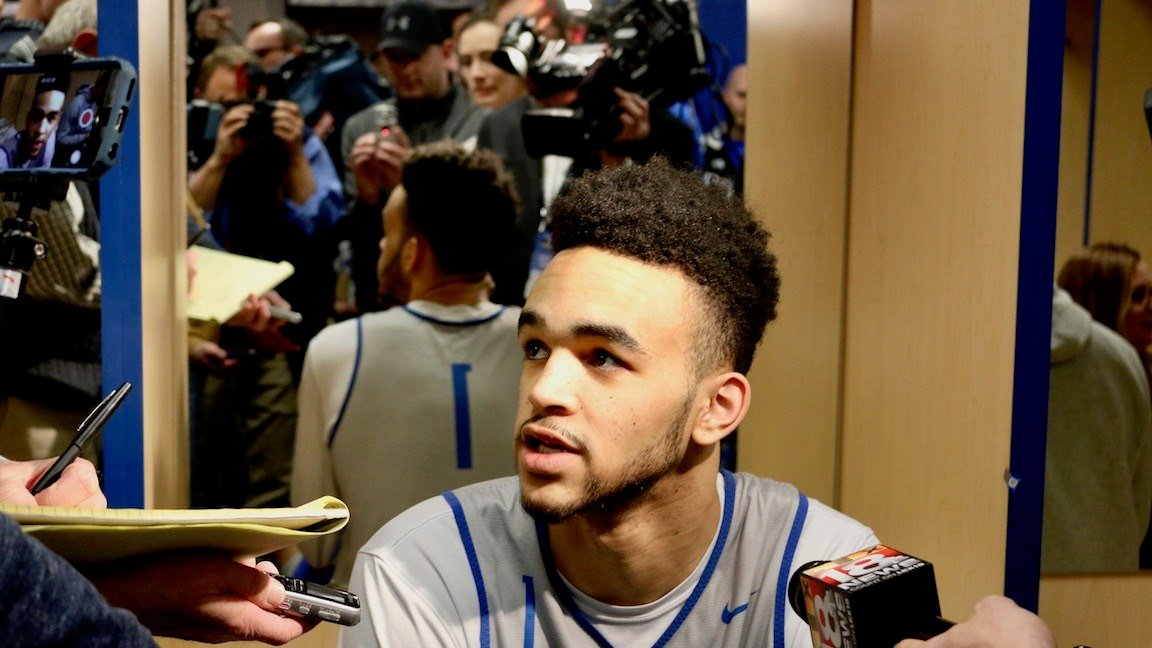 Sacha Killyea-Jones speaks with media during Friday's NCAA Tournament press availability. In the mirror behind him the media crush is depicted. (WDRB photo by Eric Crawford)
