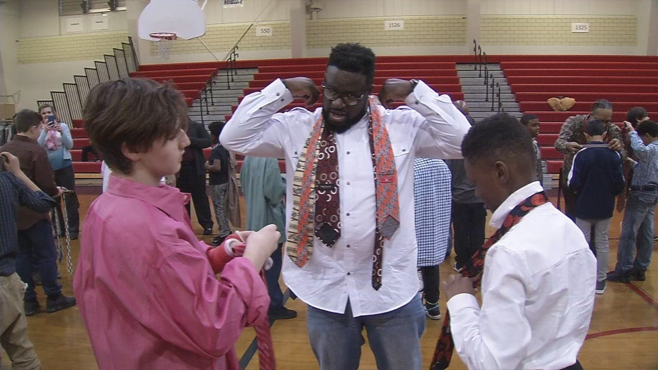 Volunteers helped students at TJ Middle School learn to tie a tie in annual event.