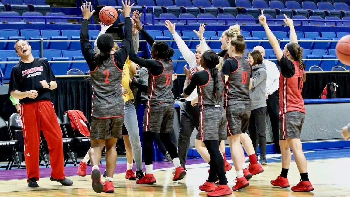 Louisville's players celebrate with ESPN's Debbie Antonelli after she beats Jeff Walz in a game of P-I-G. (WDRB photo by Eric Crawford)
