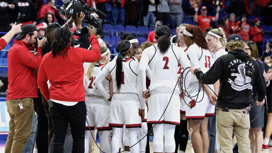 The Louisville women's basketball team huddles around coach Jeff Walz after winning in the Sweet 16. (WDRB photo by Eric Crawford)