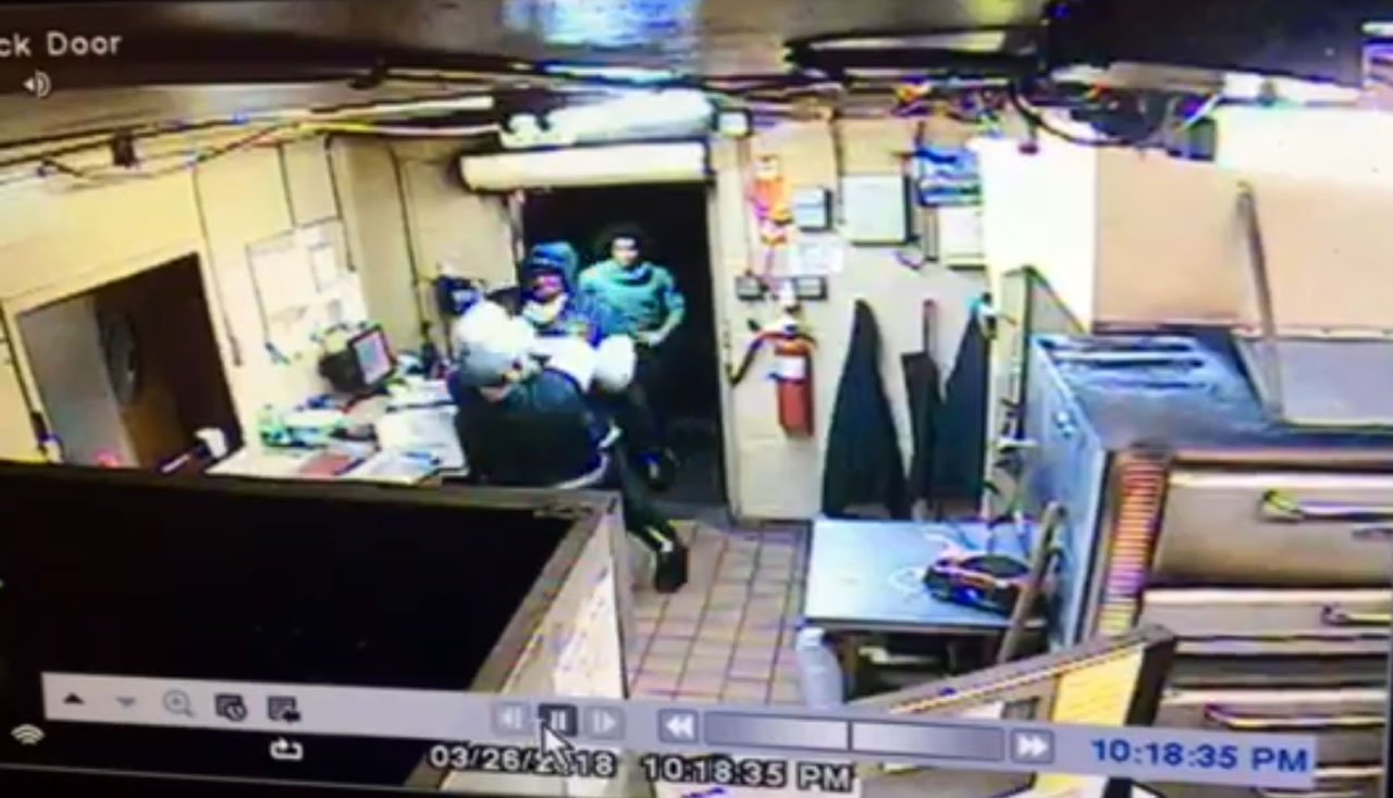 Security footage from a Sellersburg pizzeria shows two robbers barging into the business with guns, pointing them at employees, and taking off with cash.