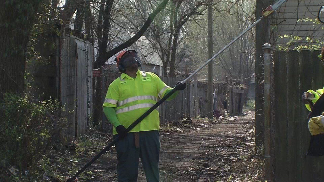 "A worker with the city of Louisville clears brush from an alleyway as part of ""Operation Clear Path"" to make it easier for police to access high-crime areas."