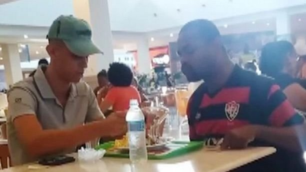 A fast food worker in Brazil is being praised for helping a man with disabilities eat his meal.