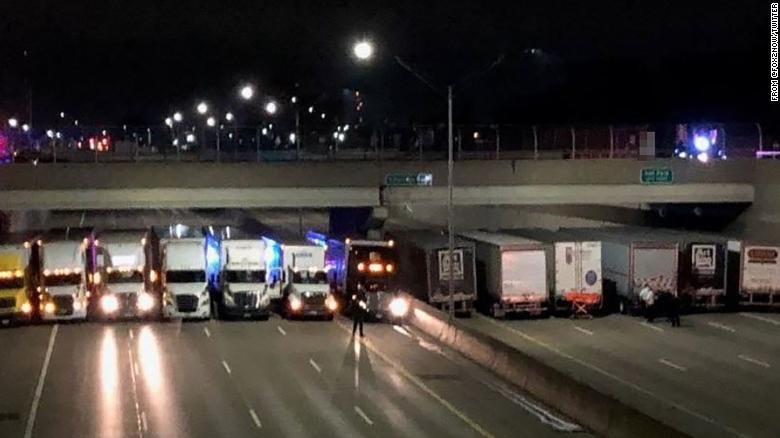 A man stood on a freeway overpass near Detroit early Thursday, threatening to jump. So thirteen tractor-trailers lined up underneath, ready to break his fall. (Photo courtesy: Twitter.com)
