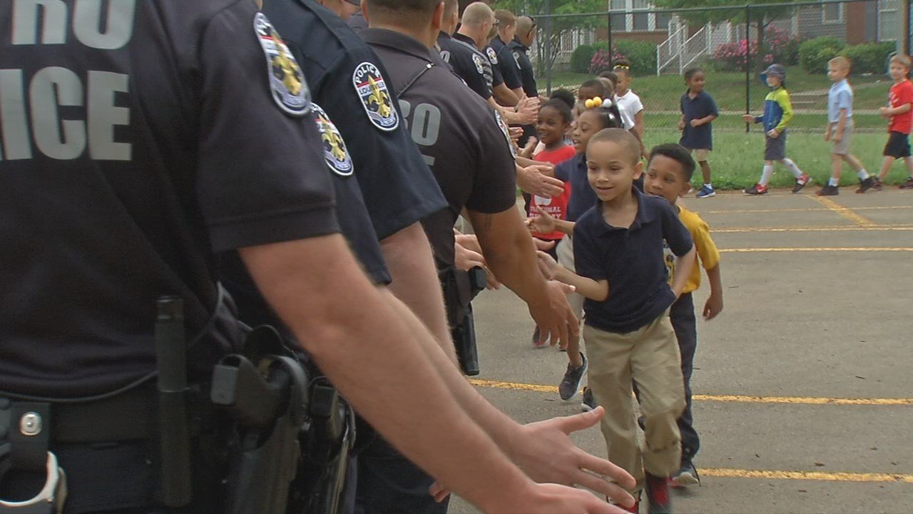 Students at Carter Traditional Elementary School greet LMPD officers with a high-five.