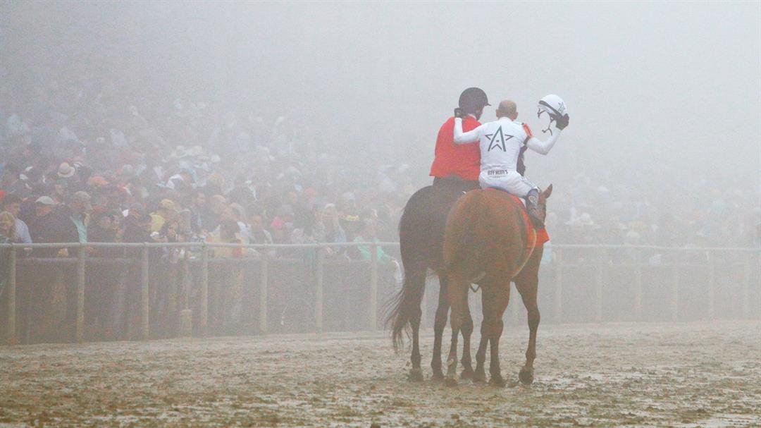 Jockey Mike Smith tips his helmet to the Pimlico crowd he can barely see after winning the Preakness Stakes aboard Justify. (WDRB photo by Eric Crawford)