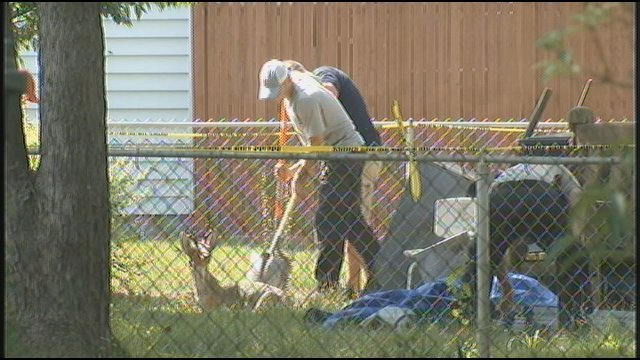 Searchers in Clyde Gibson's backyard in New Albany.  That is a concrete deer lawn ornament in the foreground.  (WDRB News image from John Hunter.)