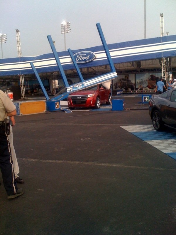 Wind-blown debris from outdoor exhibits damaged several new Ford vehicles at Kentucky Speedway Friday.