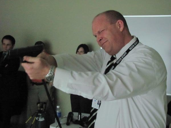 "Asst. school supt. Travis Haire aims a model firearm at a video screen during Jeffersonville police ""active shooter"" training."