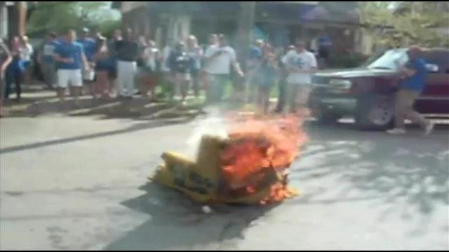 Fans jump over burning couch near UK campus in Lexington, March 30, 2012