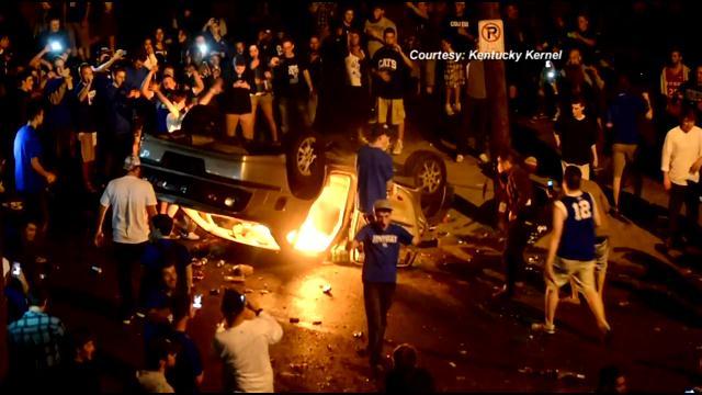 Fans surround car set afire after UK Final Four win, Lexington, March 30, 2012
