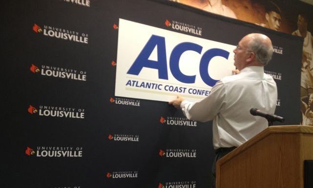 Louisville sports information director Kenny Klein hangs an ACC banner the day the Cardinals announced they had been accepted into the league.