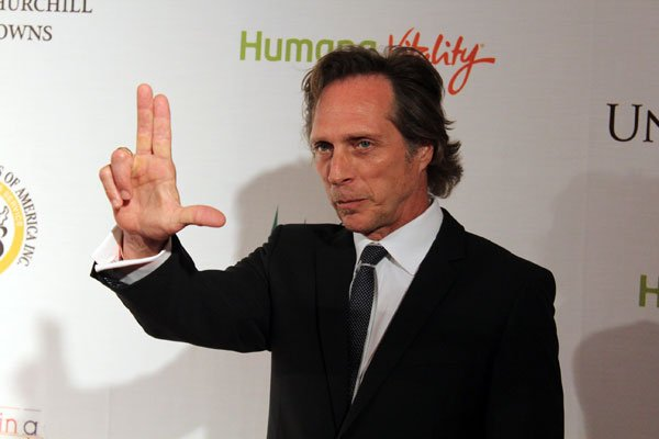"Actor William Fichtner, who has appeared in movies such as ""The Dark Knight"" AND ""Contact,"" gives the University of Louisville Cardinals hand signal."