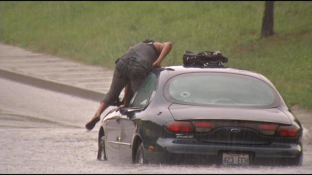 This woman was forced to abandon her car near 7th and Oak Streets during torrential rains on June 26.