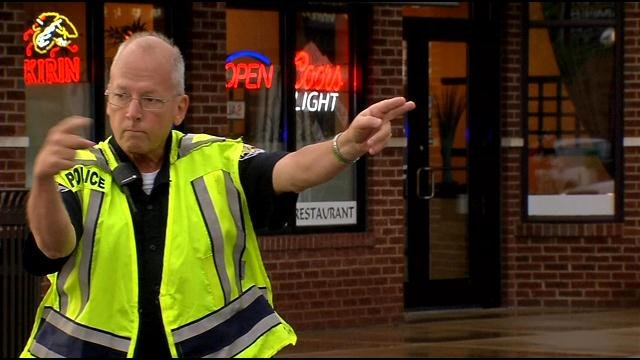 An LMPD officer directs traffic after roads were closed because of flash flooding after severe storms moved through Jefferson County.
