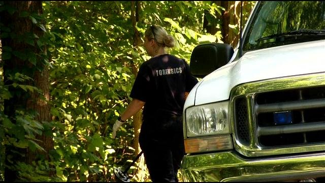 A metro police crime scene technician works Friday near Leisure Lane and Brook Bend Way in Okolona, location where a man's body was found Thursday evening.
