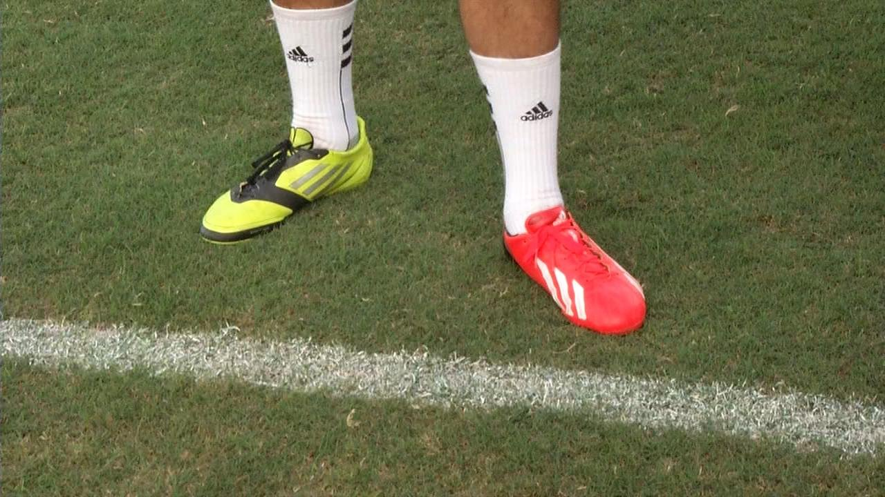 Louisville kicker John Wallace does not believe in matching cleats...or football cleats, for that matter.