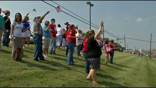 People in Radcliff raised American flags as the restored fire truck that survived the 9/11 attack at the Pentagon made its journey to Ft. Knox.