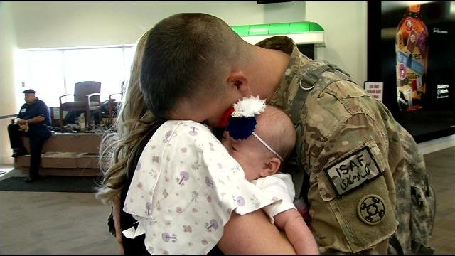 """Spc. Jimmy Eves hugs his wife, Jennifer, and their daughter,"""" Chloe Elizabeth. It was the first time he has seen her because he was deployed when she was born."""