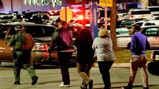 (AP Photo/Julio Cortez). An official, left, wearing tactical gear leads a group of people out of the Garden State Plaza Mall during a lockdown following reports of shots fired in Paramus, N.J.